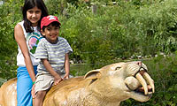 Children riding a play saber tooth tiger